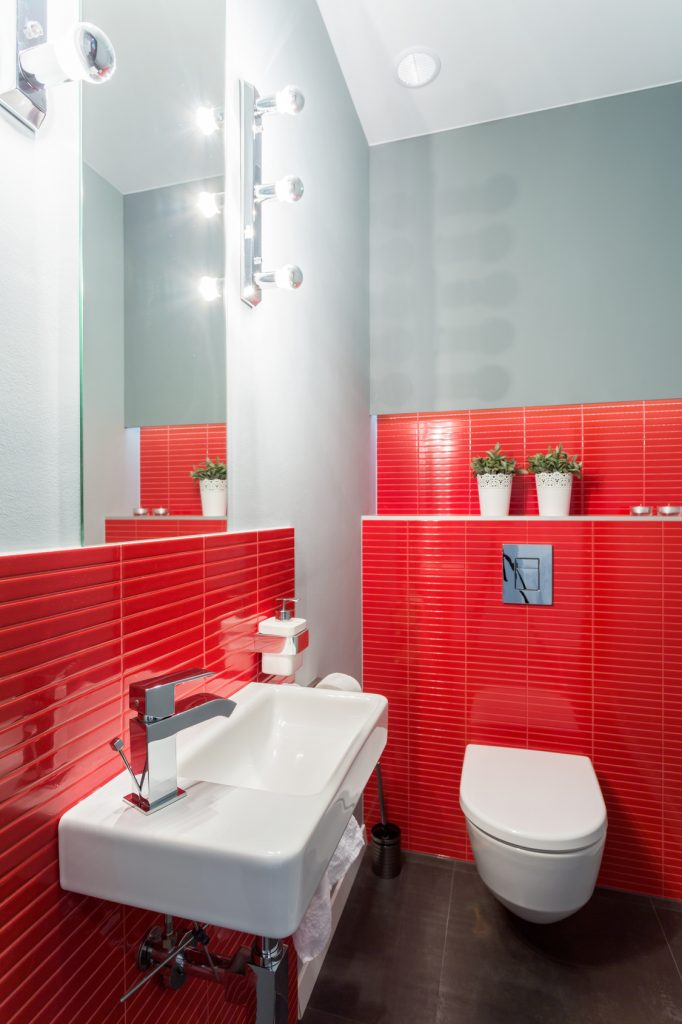 Red toilet with bowl and sink